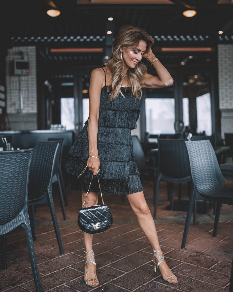 Holiday Party look featured by top Indianapolis fashion blogger, Karina Style Diaries: image of a woman wearing a Lesley Jane black fringe dress, Manolo Blahnik heels, Chanel bubble bag, Daniel Wellington watch and Jemma Sands drop earrings
