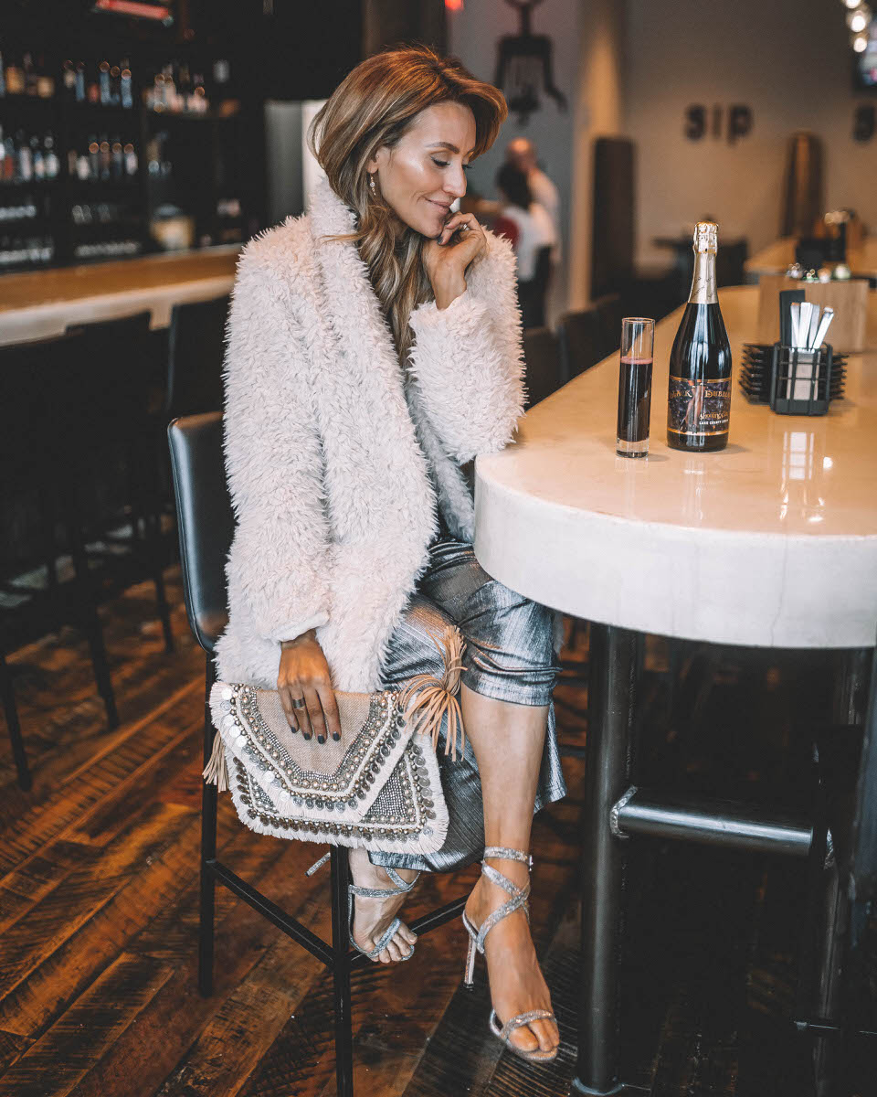 Top Indianapolis fashion blogger, Karina Style Diaries, features the perfect Holiday look with a BB Dakota metallic Jumpsuit: image of a blonde woman wearing a BB Dakota metallic jumpsuit, a BB Dakota faux fur coat, a Sashi clutch and Manolo Blahnik silver heels