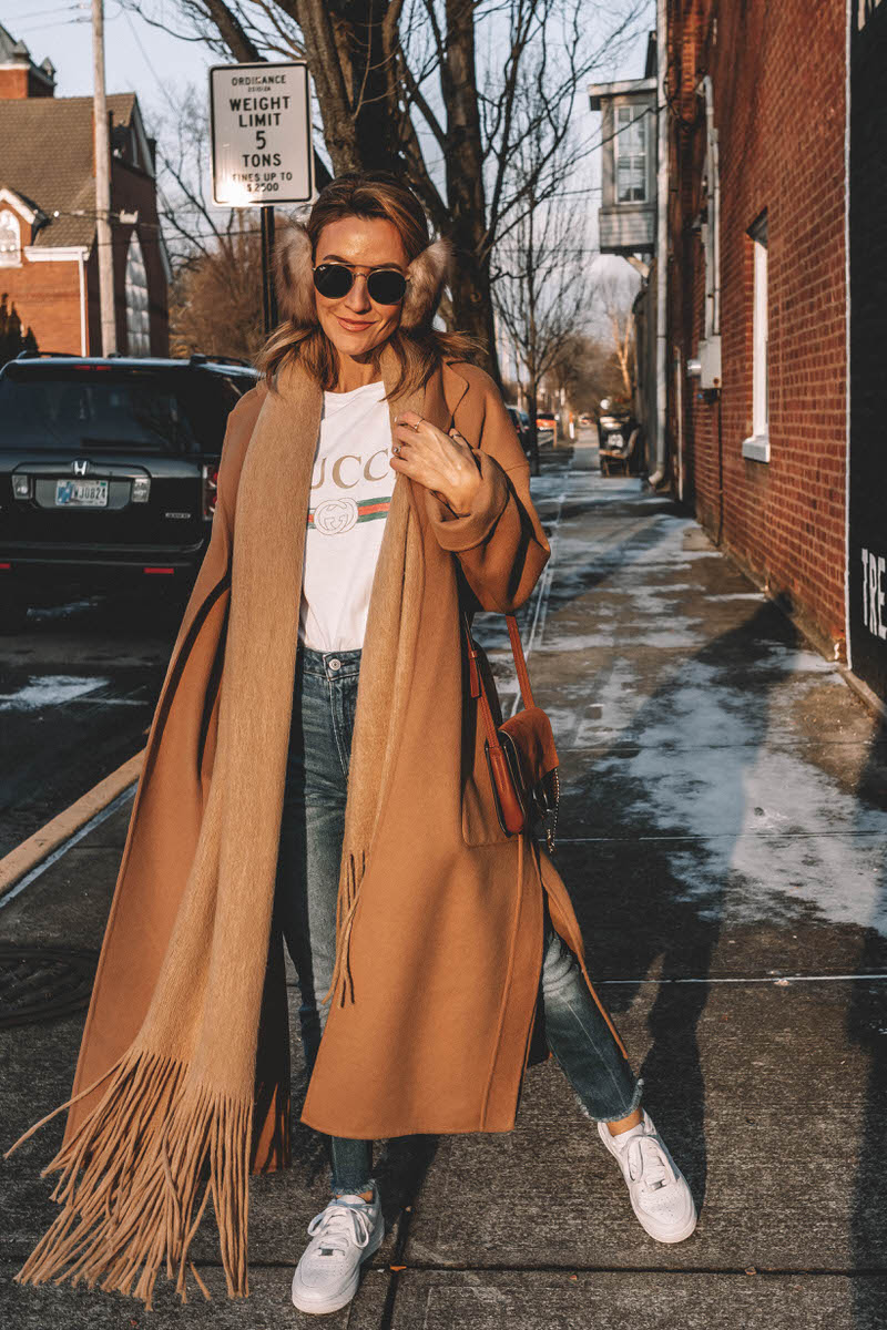 Fashion Blogger Karina Reske wears Camel Coat | Gucci t-shirt | nike air force 1 white | fur earmuffs | round ray bans | Zara camel coat styled by top US fashion blogger, Karina Style Diaries: image of a woman wearing an oversized Zara camel coat, distressed Gucci tee, Abercrombie and Fitch high waisted jeans, Nike Air Force 1 sneakers, Ray Ban aviator sunglasses, faux fur earmuffs and Chloe leather shoulder bag