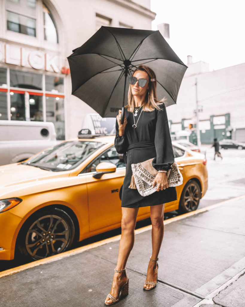 Fashion Blogger Karina Reske in a Vici Black Dress | embellished clutch | leopard print slides | holding an umbrella | street style | NYFW NYFW outfits and tips featured by top US fashion blogger, Karina Style Diaries: image of a woman wearing an Express black neck dress, ASOS leopard sandals, Shashi clutch and a Gorjana pendant necklace