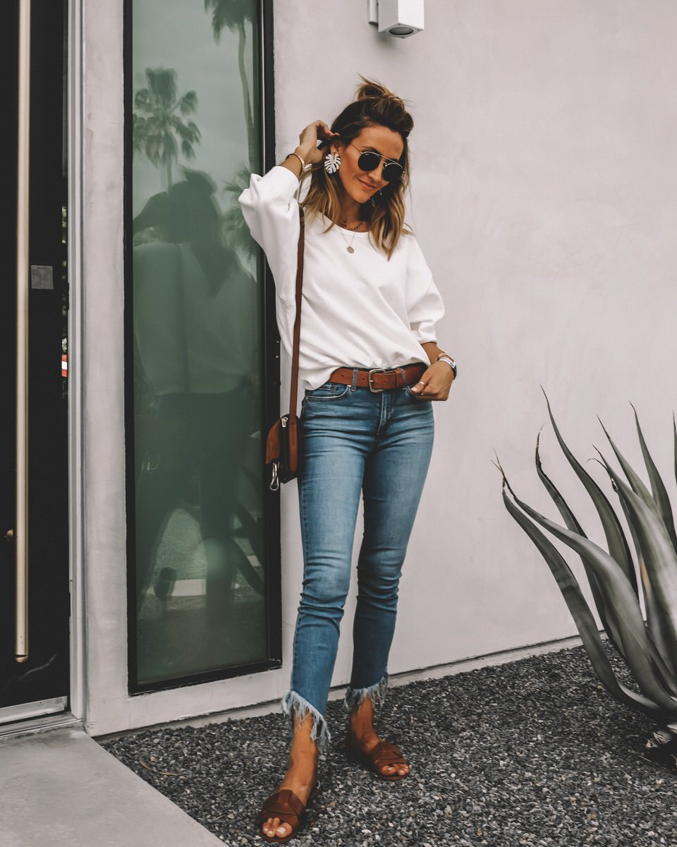 Fashion blogger Karina Reske | denim look | white sweatshirt | fringe jeans | palm leaf white earrings | travel outfit idea | Sofía Vergara Jeans