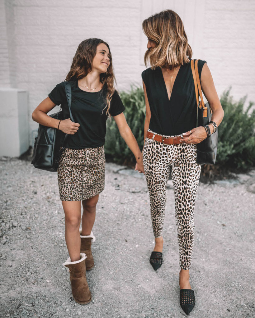 Karina Reske and daughter Sophia back to school mommy and me outfit ideas leo print pants and skirt black top black backpack uggs