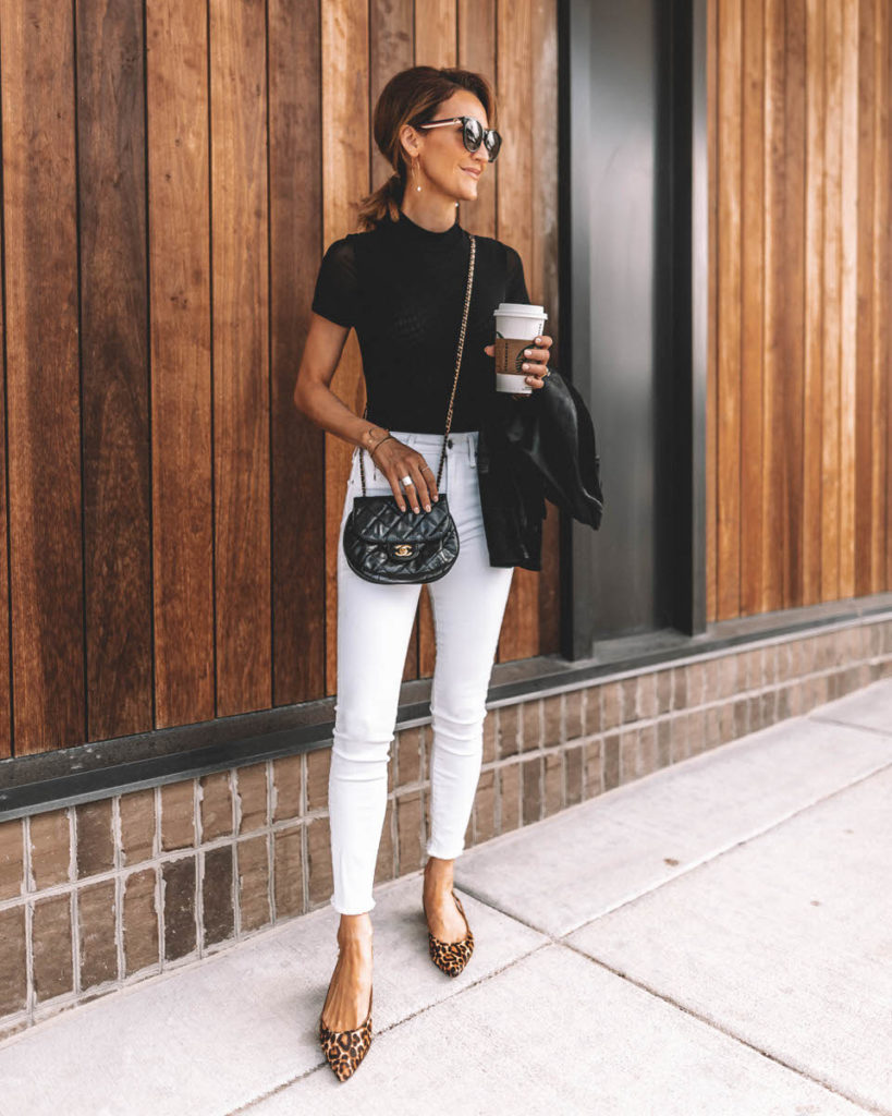 Karina Reske wearing white skinny jeans black bodysuit chanle buble crossbody leopard shoes pointy flats leather suede moto jacket black and white chic outfit idea