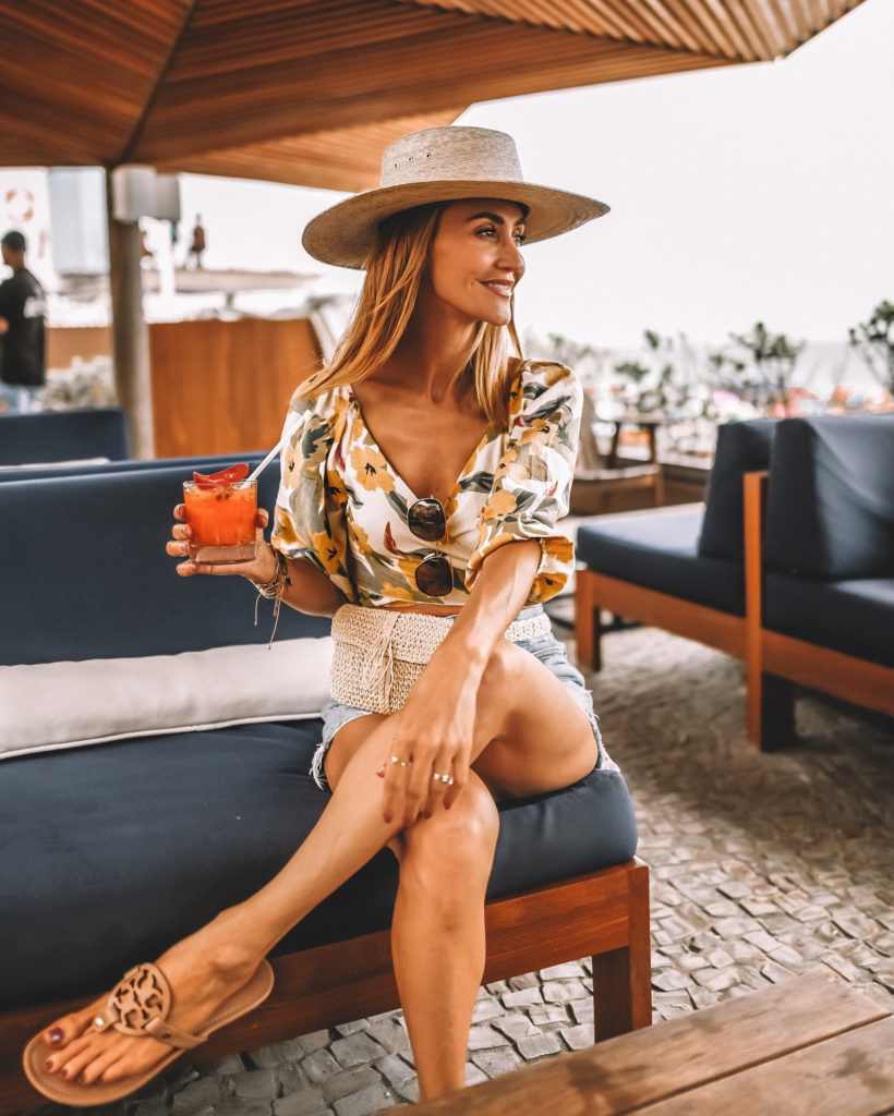 Karina Style Diaries wearing floral wrap top Agolde shorts straw hat sipping caipirinhas in Ipanema