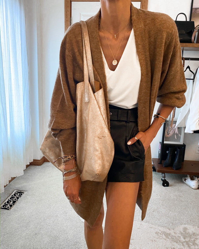 Fashion blogger Karina Style Diaries wearing leather shorts v-neck tee oversized cardi gold suede tote