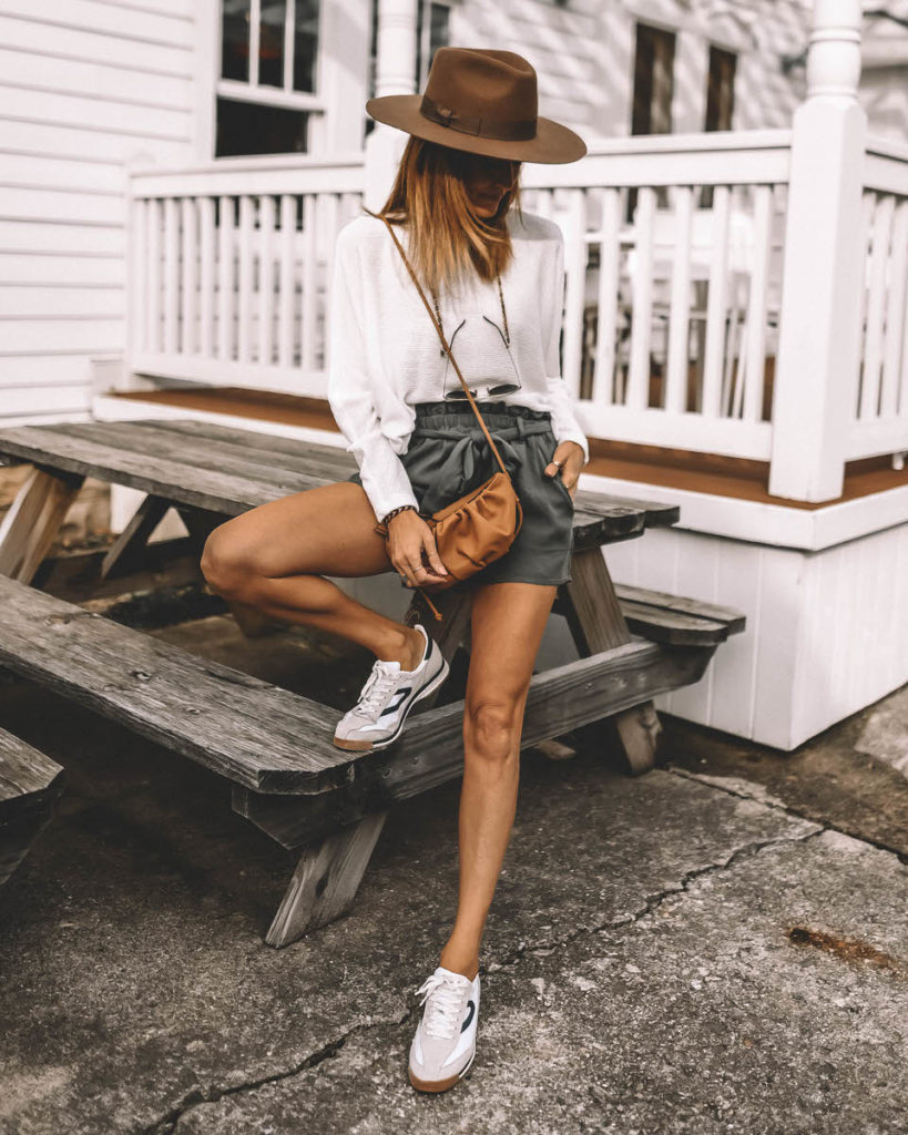 Karina Style Diaries wearing sage paperbag shorts tretorn sneakers western hat dolman sleeve white sweater spring outfit