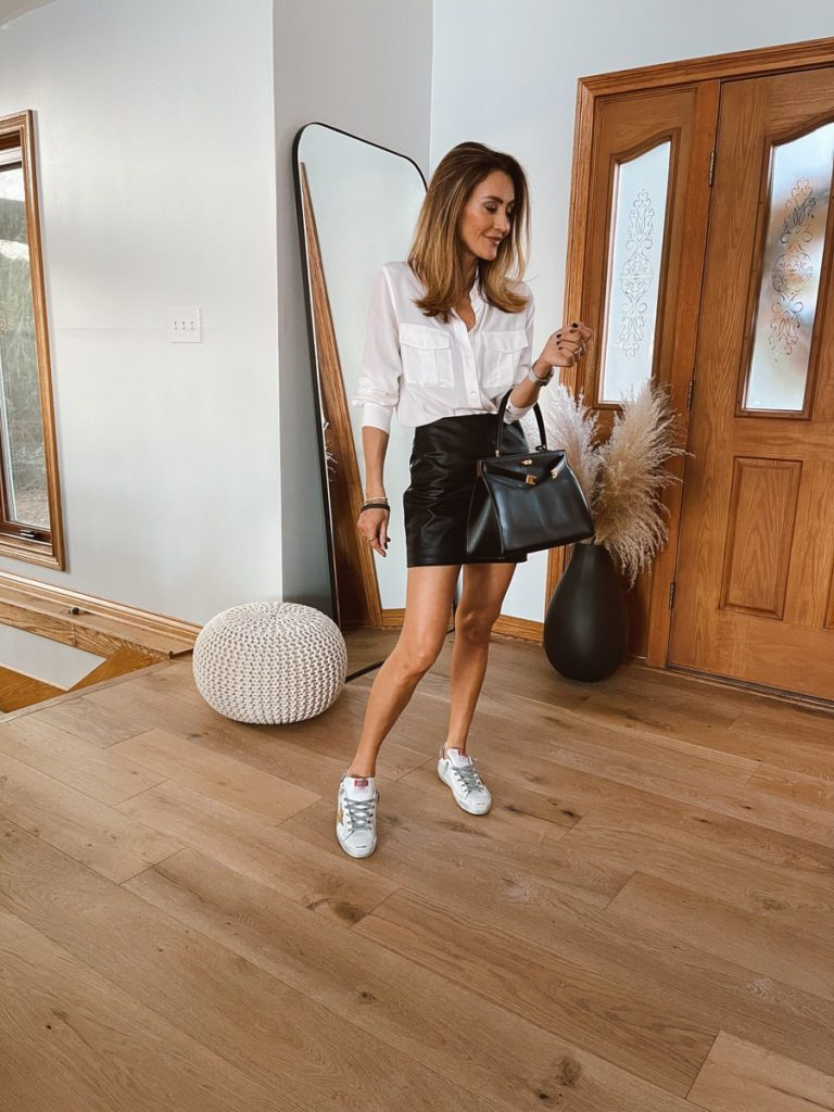 Karina Style Diaries wearing leather mini skirt silk button down golden goose sneakers tory burch bag neutral style