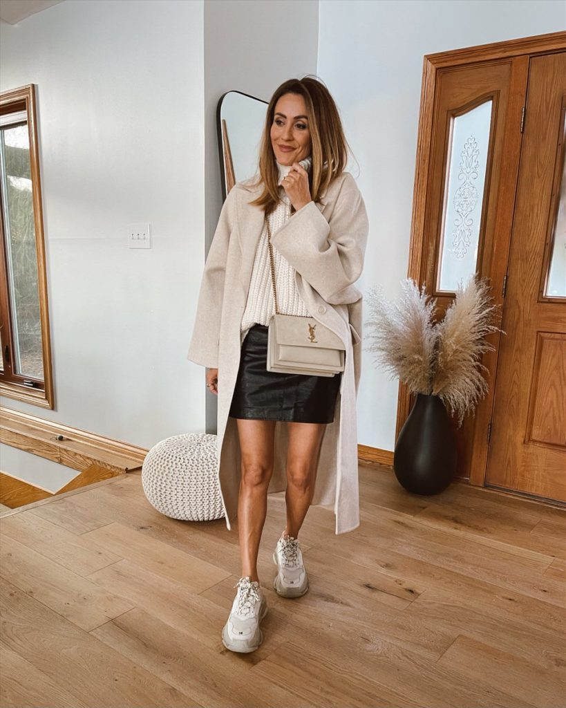 Karina Style Diaries wearing leather mini skirt sleeveless sweater oversized coat balenciaga sneakers ysl bag neutral style